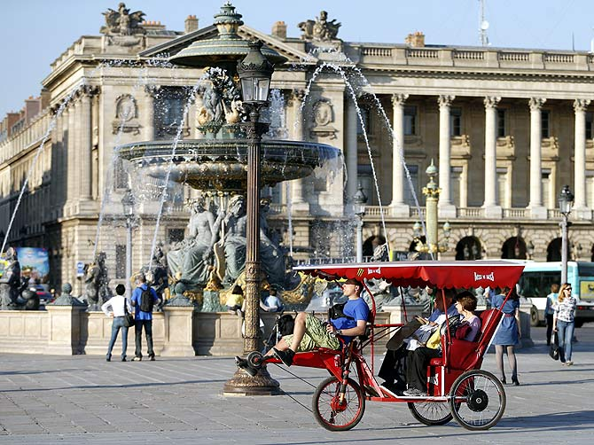 A velo taxi, concept based on the Asian rickshaw, drives tourists through the Place de la Concorde in Paris.