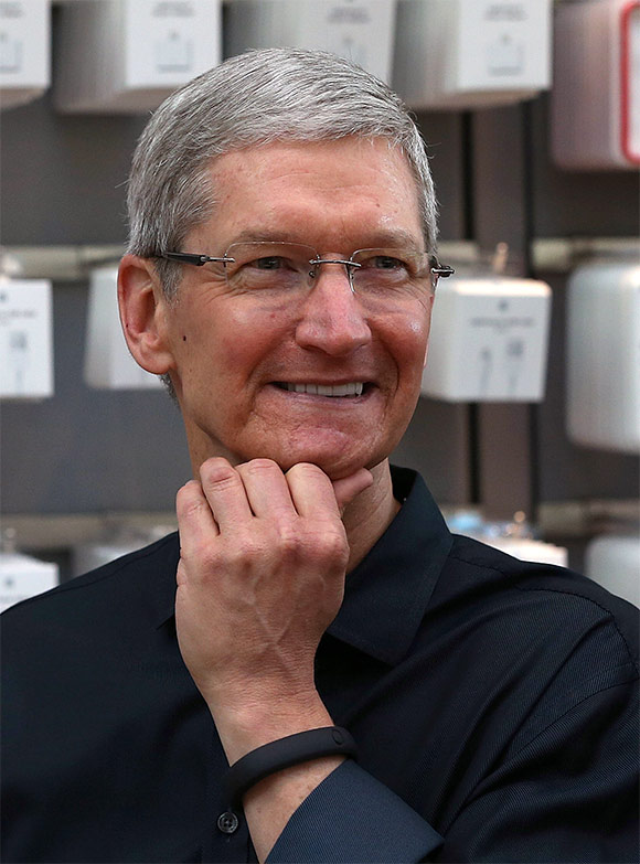 Apple CEO Tim Cook looks on before the Apple Store opens.