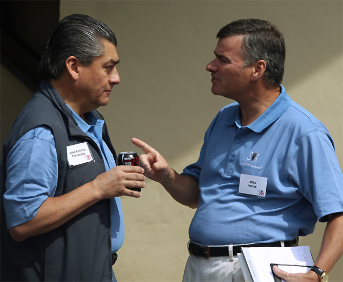 DirecTV chairman, president and chief executive Mike White (R) gestures while speaking with FEMSA chairman and chief executive Jose Antonio Fernandez.