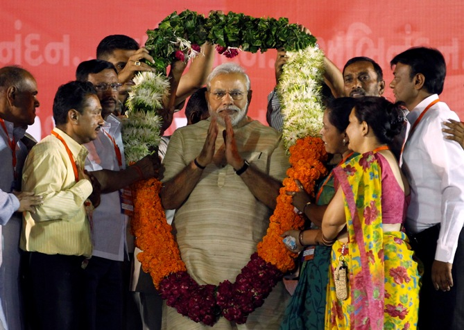 Prime Minister-designate Narendra Modi wears a garland presented to him by his supporters at a public meeting in Ahmedabad.