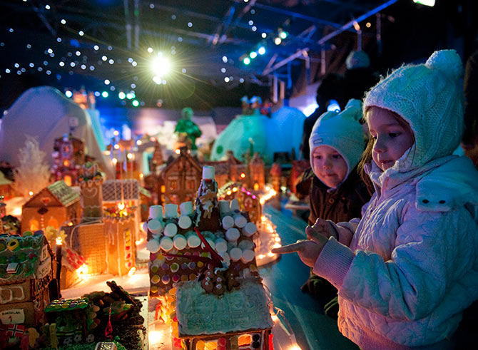 Children look at a gingerbread town consisting of buildings, boats, bridges and other structures, in Bergen.