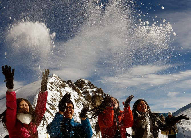 Tourists from Singapore throw up snow as they pose for a photograph in front of Mount Titlis.