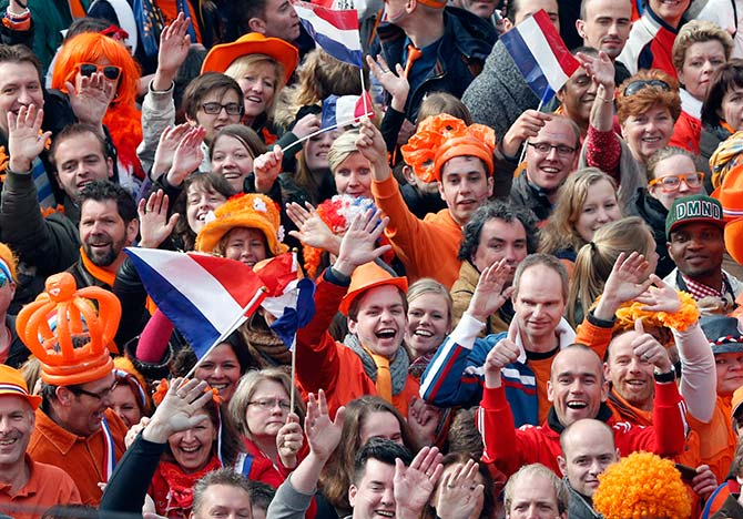 People wave hands as they celebrate the new King Willem-Alexander who succeeds his mother Queen Beatrix, in Amsterdam's Dam Square.