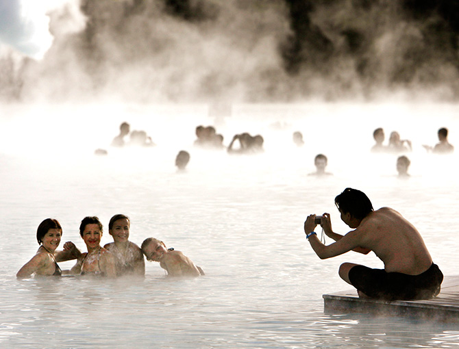 Bathers pose for a photo as they swim in the geothermal hot springs at Iceland's Blue Lagoon near Grindavik.