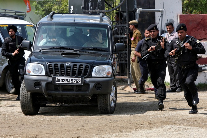 Security personnel of Prime Minister Narendra Modi run next to a car carrying Modi, upon his arrival to address a rally.