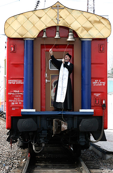 An Orthodox priest rings the bells on the church carriage of the Doctor Voino-Yasenecky Saint Luka train.