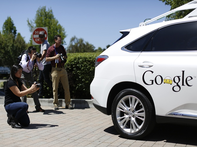 Members of the media take photos of a Google self-driving vehicle at the Computer History Museum after a presentation in Mountain View, California.