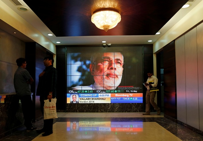 People look at a screen displaying the election results coverage on a screen inside the Bombay Stock Exchange building in Mumbai May 16, 2014.