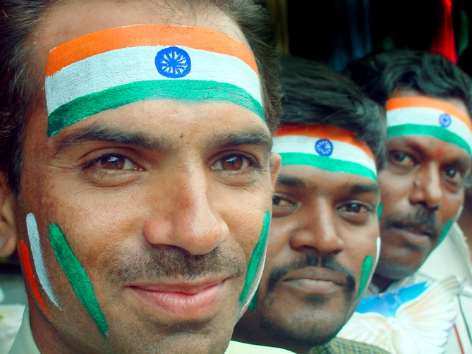 Indian men with their faces painted in the Indian tricolour.