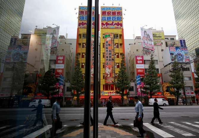 People are reflected on a window as they walk through Tokyo's Akihabara district in Tokyo.