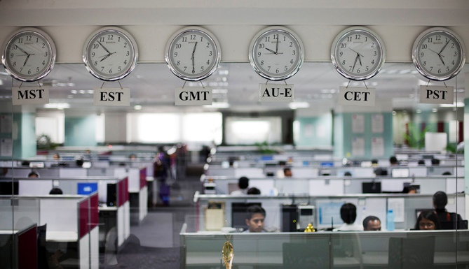 Workers are pictured beneath clocks displaying time zones in various parts of the world at an outsourcing centre in Bengaluru.