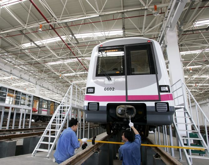 Technicians service a train in a station during a media visit to the new Shanghai Metro Line.