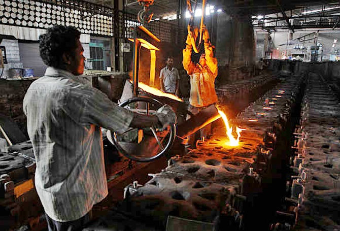 Workers tend to a furnace at a steel factory.