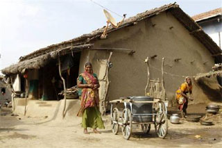 Image: Villagers smile outside their mud house in Khun village near Dholera town in Gujarat. Photograph: Amit Dave/Reuters