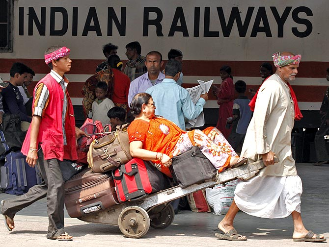 Porters ferrying a passenger at a railway station in India.