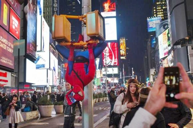 A man in a Spider-Man costume hangs upside down from digital cross walk signs in Times Square during Halloween, in New York.