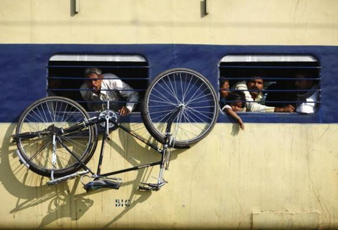 A bicycle hangs from the window of a train at Parsha Bazar railway station in Bihar.