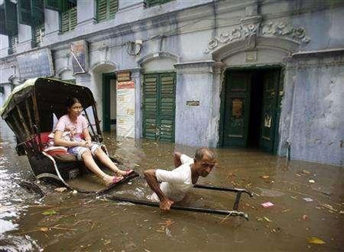 Image: A rickshaw puller transports a girl through a flooded street in Kolkata. Photograph: Jayant Shaw/Reuters