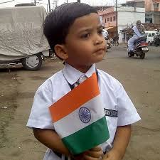 A school boy holds the national flag.