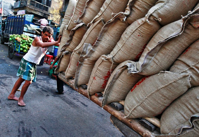 A labourer pushes a hand cart loaded with sacks of rice at a wholesale market in Kolkata.