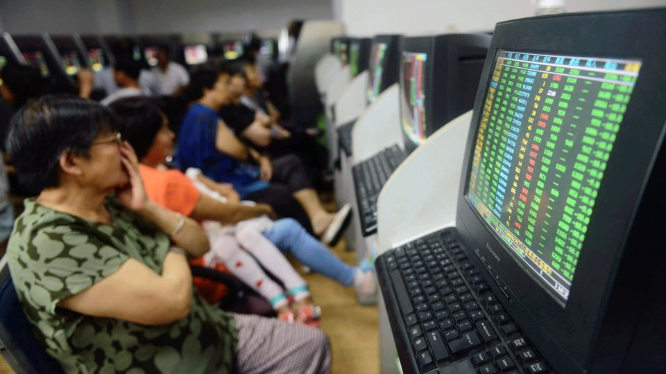 Investors sit in front of computer screens showing stock information at a brokerage house in Qingdao.