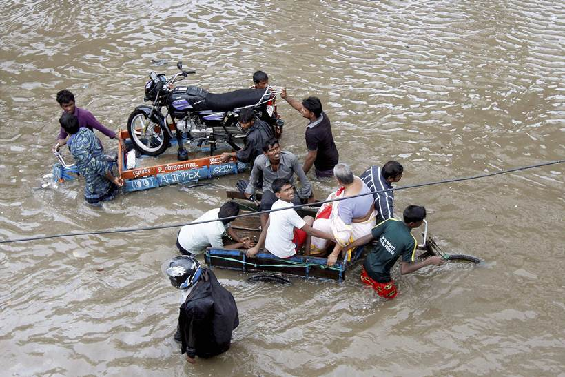 People help a man carry his two-wheeler on a cycle cart as they wade through a waterlogged subway in Chennai.