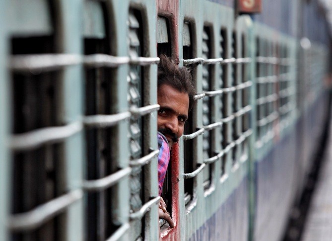 A passenger looks out from the window of a stationed train at a railway station in Jammu.