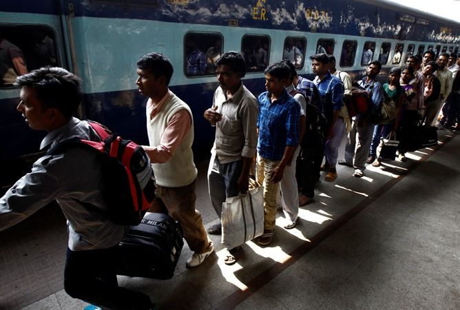Commuters line up to board a passenger train at a railway station in Kolkata.