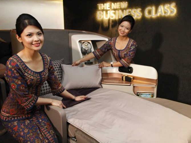 Singapore Airlines flight attendants show off a new business class seat.