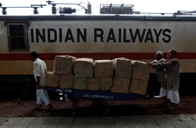 Porters transport goods on a hand-pulled trolley to load onto a train at a railway station in Kolkata.