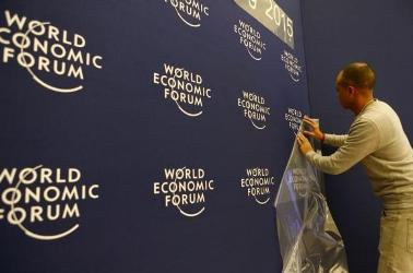A worker sets up logos of the World Economic Forum (WEF) at the congress center in the Swiss mountain resort of Davos January 20, 2015.