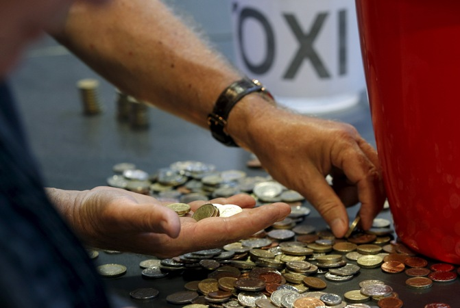 Donations of cash are counted following a collection for the Greek Solidarity Campaign, during a rally in support of Greece at the TUC's Congress House, in London, Britain, July 6, 2015.