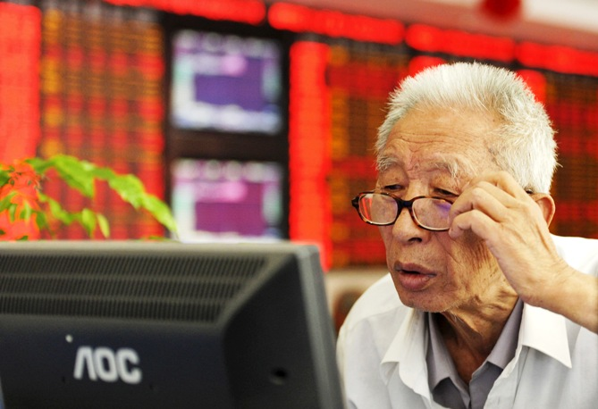 An investor adjusts his glasses as he looks at a computer screen in front of an electronic board showing stock information at a brokerage house in Fuyang, Anhui province, China