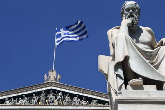 A Greek flag flutters behind a statue of ancient philosopher Socrates at the the Academy of Athens.