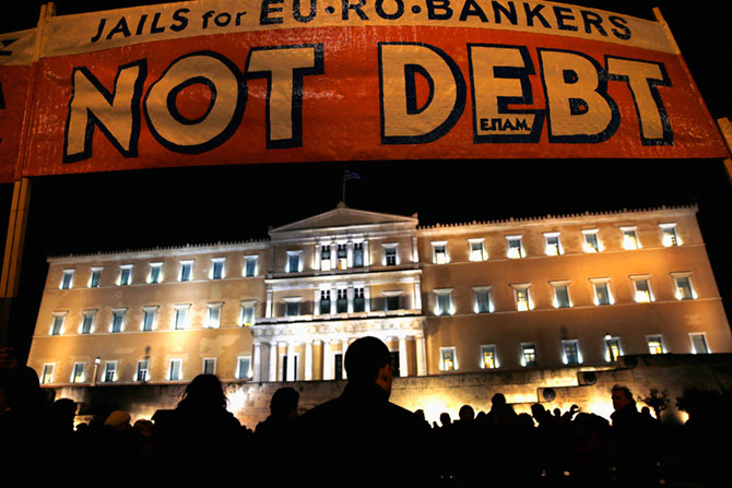 People are silhouetted in front of the parliament during an anti-austerity pro-government demonstration in Athens February 16, 2015. Greece and its creditors made little progress in recent days toward an interim funding deal, officials involved in the talks said, citing wide differences over how the Athens government can deliver on election promises and satisfy lenders.