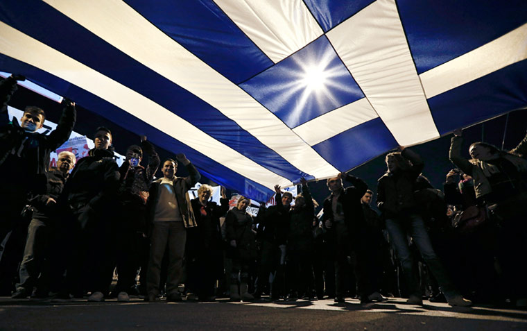 Protesters hold a giant Greek national flag during an anti-austerity and pro-government demonstration in front of the parliament in Athens February 15, 2015. Greece recently said it was confident of reaching agreement in negotiations with its euro zone partners but reiterated it would not accept harsh austerity strings in any debt pact. Alkis Konstantinidis/Reuters