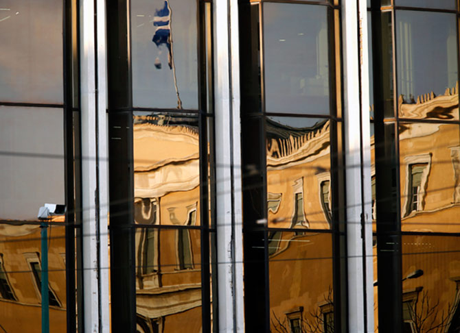 The Greek parliament is reflected on the Foreign Ministry building in Athens March 12, 2015. Greece has promised its lenders to reform its state sector, to implement labour reforms, such as opening up closed professions, to make its economy more competitive, improve its tax administration and fight tax evasion and corruption, which have been widely blamed for the debt crisis. REUTERS/Yannis Behrakis