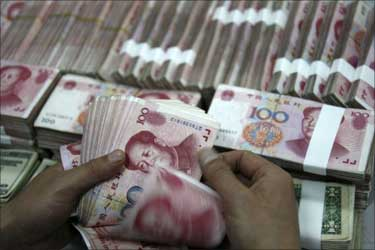 An employee counts yuan banknotes at a branch of the Industrial and Commercial Bank of China.