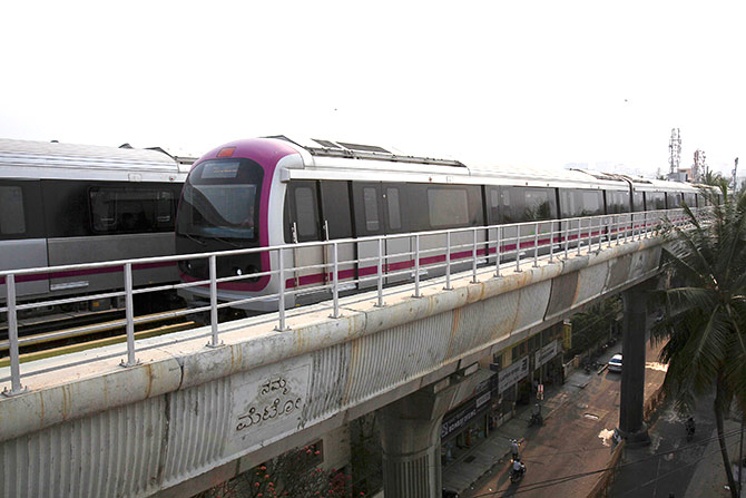 "A Namma Metro (Kannada for ""Our Metro"") train travels along an elevated track in the Indira Nagar area of Bengaluru"