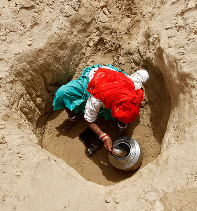 Image: A woman fills a pitcher with drinking water from a hole made in the dried-up Banas river bed near Sukhpur village, north of Ahmedabad. Villagers walk two and a half kilometres to draw drinking water from them, and they say it takes 30-40 minutes to fill a five-litre jar. Photograph: Reuters