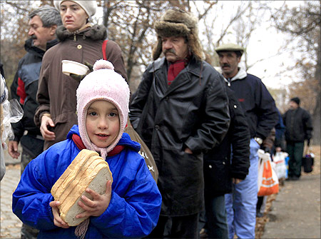 A girl receives bread from Krishna followers in Budapest.