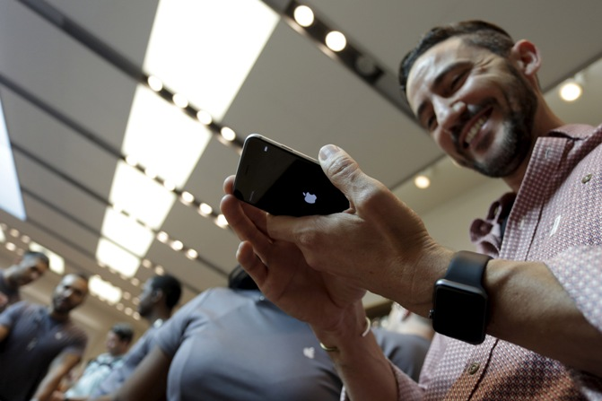 A man holds an iPhone 6s Plus as the Apple iPhone 6s and 6s Plus go on sale at an Apple Store in Los Angeles, California
