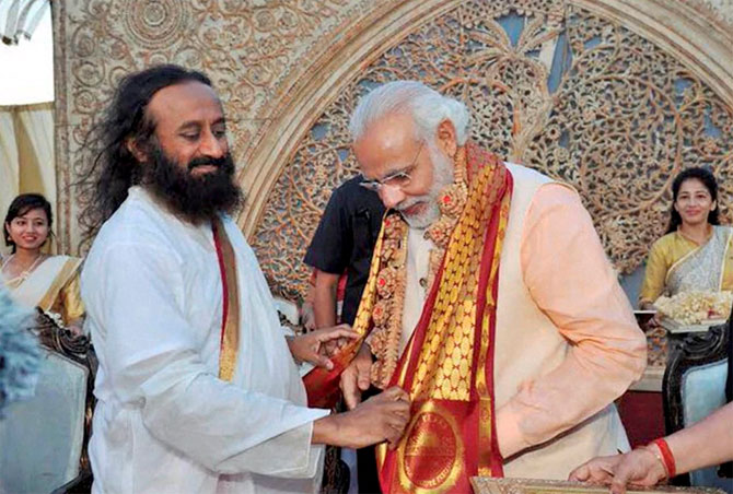 Prime Minister Narendra Damodardas Modi greeted by Art of Living founder Sri Sri Ravishankar on the opening day of the World Culture Festival on the banks of the Yamuna in New Delhi. Photograph: PTI