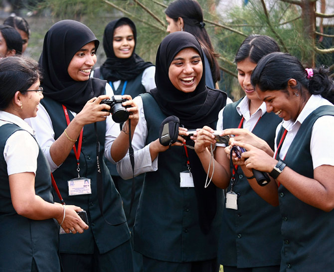 IMAGE: Students from the Federal Institute of Science and Technology (FISAT) laugh while reviewing their portraits before participating in a competition on self-portrait photographs at the college campus in Angamaly, Kochi.