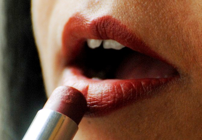 A woman puts on lipstick at a beauty parlour.
