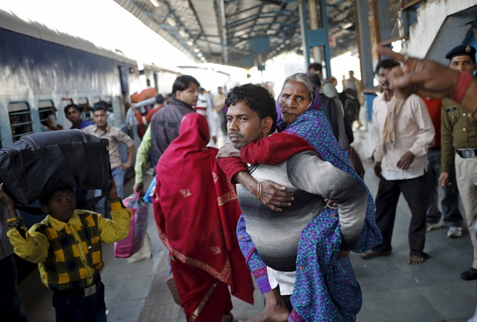 A man carries his mother to board a passenger train at a railway station in New Delhi, February 25, 2016.