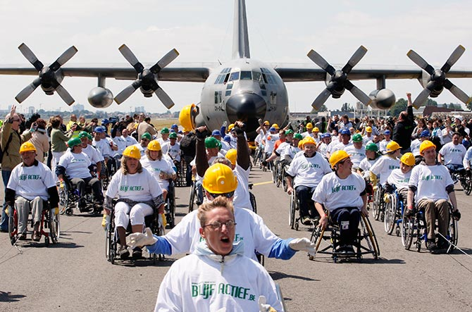 People in wheelchairs pull a C130 cargo aircraft weighing 67 tons across 100 metres at the Melsbroek military airport near Brussels May 29, 2011. The attempt, led by 84 people, set a new Guinness World Record for heaviest plane pulled over 100 metres by a team of people in wheelchairs. Photo: Sebastien Pirlet/ReutersTERS/