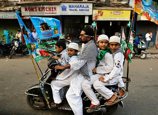 Muslims ride on a scooter on their way to participate in a procession to mark Eid-e-Milad-ul-Nabi
