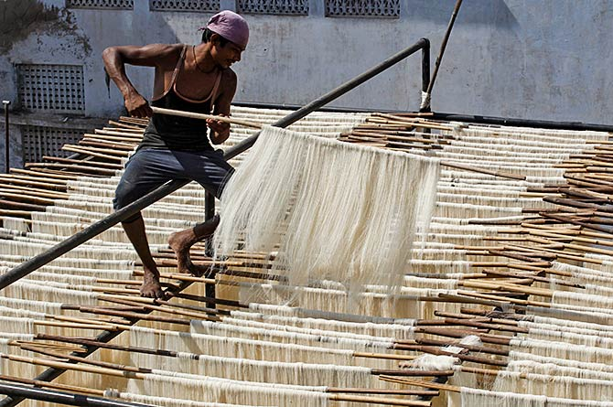A man hangs strands of vermicelli to dry at a factory in Allahabad, India, June 29, 2016. Photo: Jitendra Prakash/Reuters