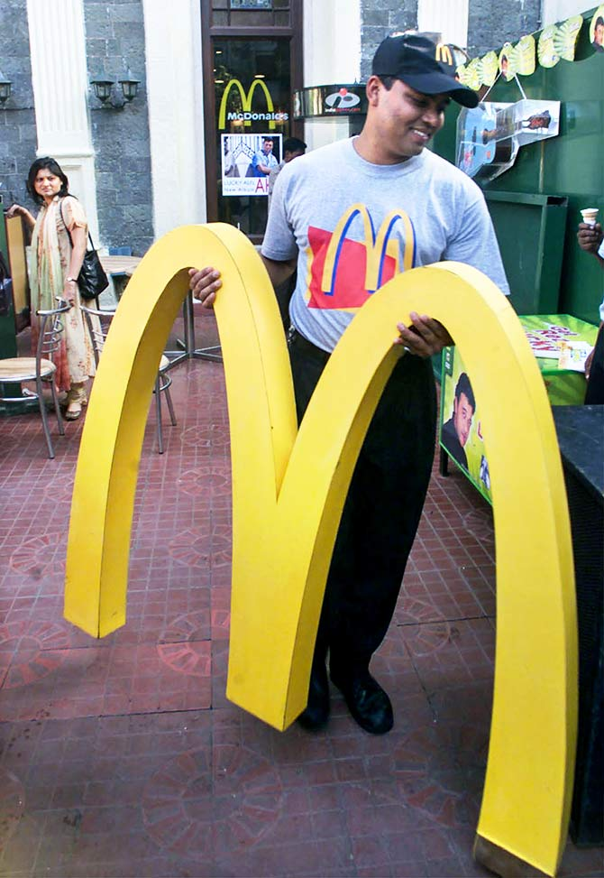 A worker carries the famous golden arches in front of McDonalds restaurant in Bombay. December 5, 2000. Photo: Savita Kirloskar/Reuters